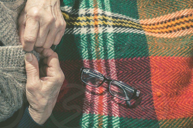 Elderly woman buttoning his vest. Glasses on blanket photo