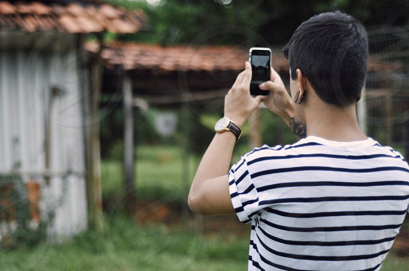 person holding cell phone taking picture of home photo