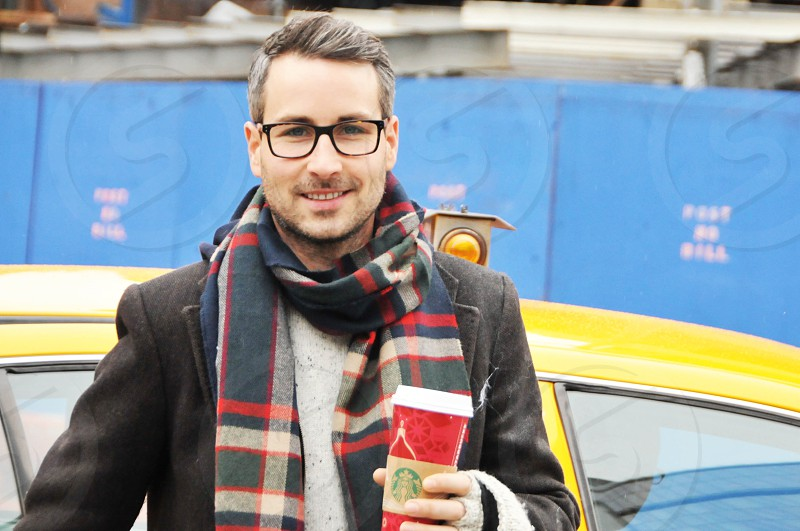 young business man professional drinking Starbucks in front of yellow cab photo