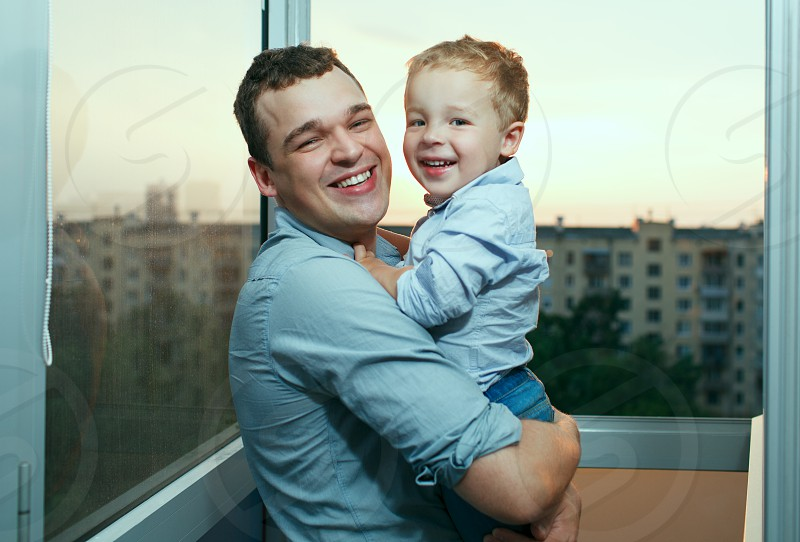 Young father holds a three year old son on the balcony. Laughing and smiling. photo