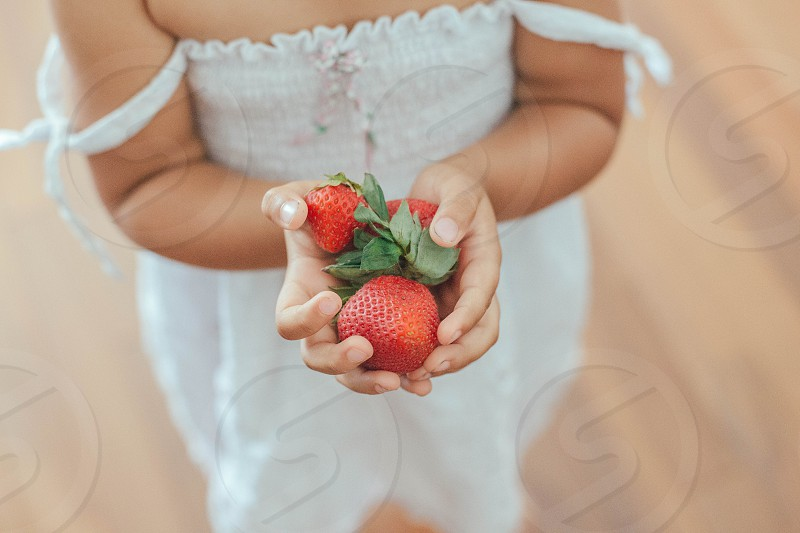 view of children holding a cherry fruit photo