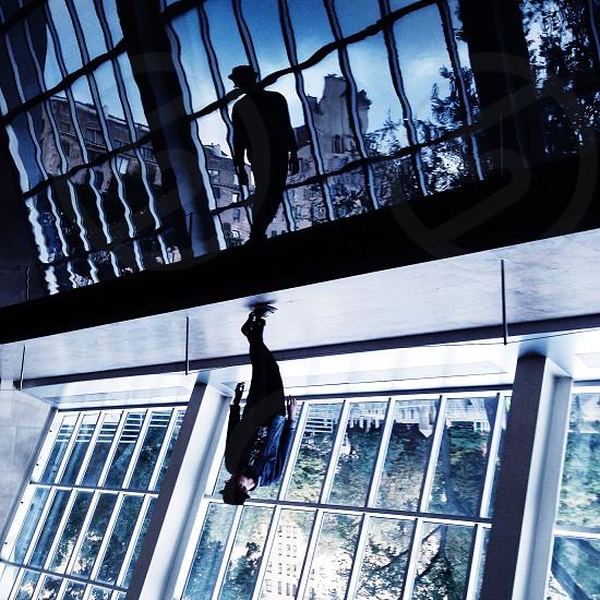 man in black fedora near mirrored reflective windows photo