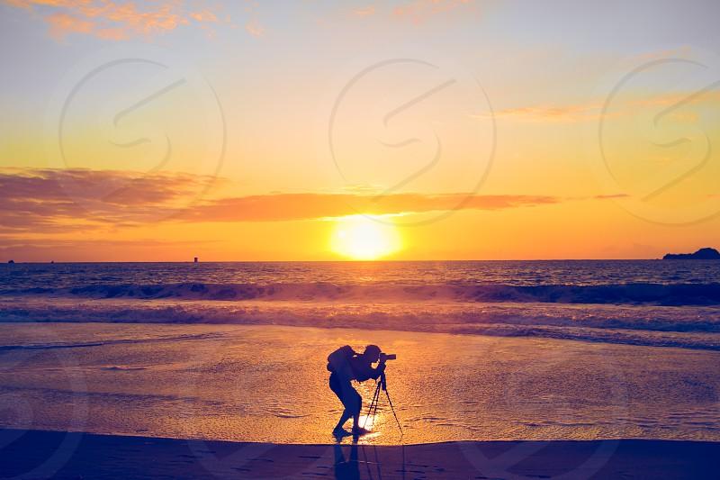 photographer shadow silhouette sunset ocean color yellow orange glow tripod sun pose man focus bag pack baker beach San Francisco california  photo