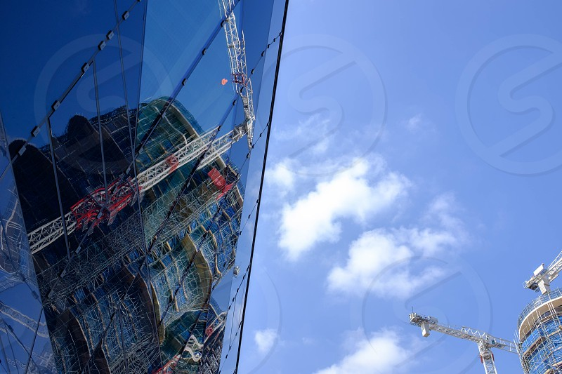 Reflected image of a construction site and crane in a shiny modern office window with blue sky behind photo