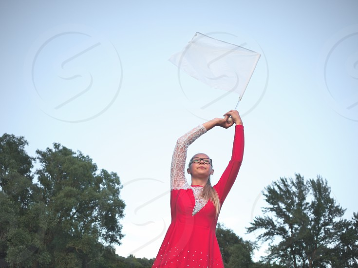 Bespectacled Blonde Teen Majorette Girl with White Flag Outdoors in Red Dress photo