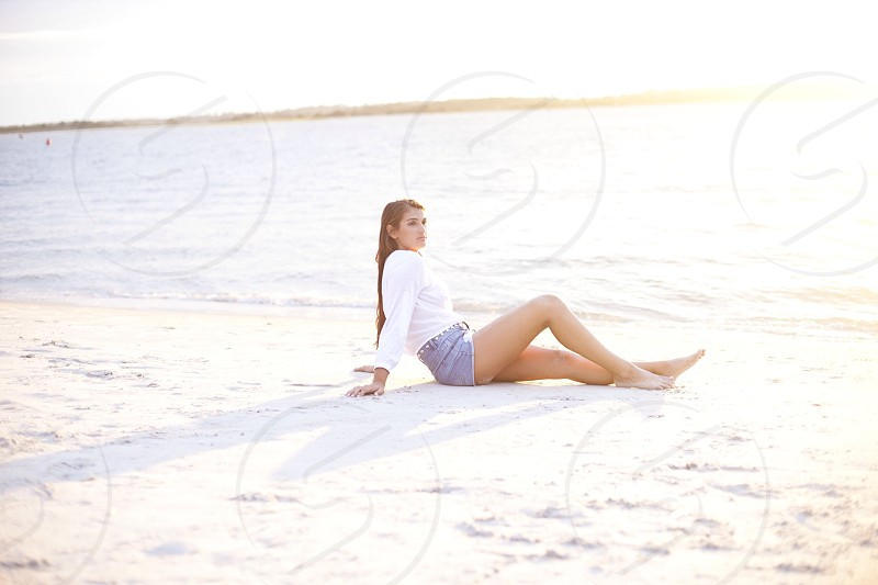 woman in white long sleeve shirt and blue denim shorts sitting on the shore photo