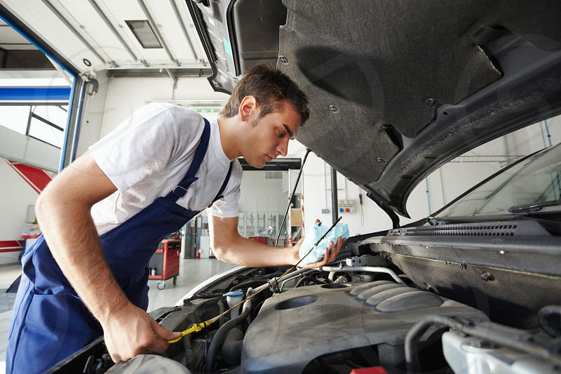 mechanic; man; car; checking; oil; change; working; repairing; engine; people; one person; male; Caucasian; young; adult; young man; 30s; serious; concentration; side view; looking; examining; holding; indoors; garage; auto repair shop; manual worker; transportation; transport; vehicle; auto; automobile; hood; motor vehicle; broken car; oil change; routine; motor oil; engine oil; car repair; fixing; expertise; skill; work; service photo