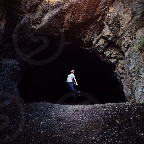 person jumping near cave portrait photo