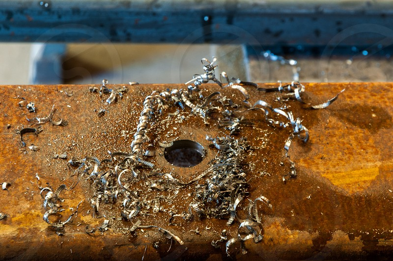 Rusted steel with drilled hole and shavings photo