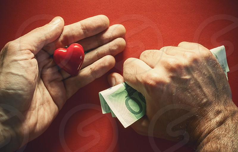 Conceptual composition about love or money two male hands one holds money tightly and other red heart as symbol of love.  photo