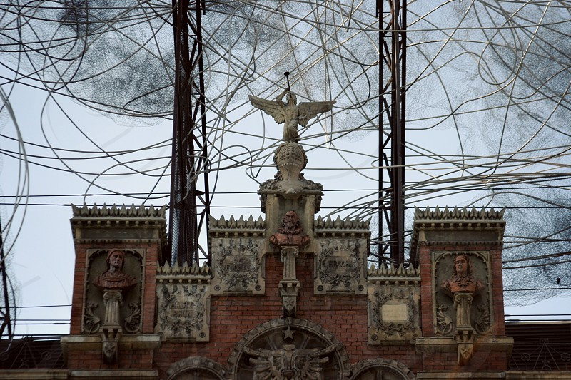 Unique building in Barcelona Spain. Statue trumpet angel classic gothic modern art cables wires mesh busts castle brick. photo