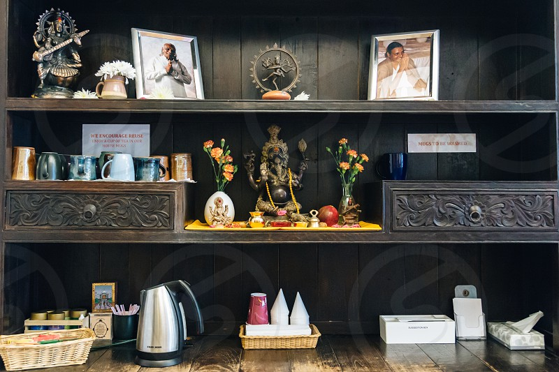 photo frame and buddha figurine and grey electric kettle in the shelf photo