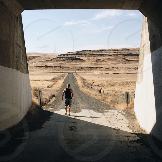 man running underneath cement tunnel in the dester photo