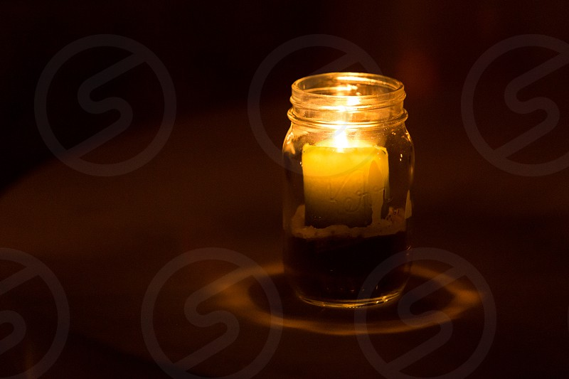 A glowing candle in a mason jar photo