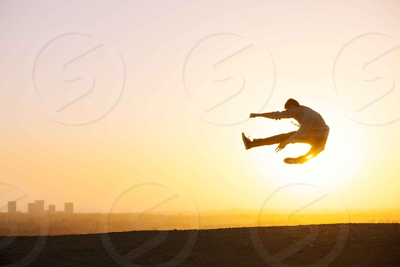 man jumping in sunsest portrait photo