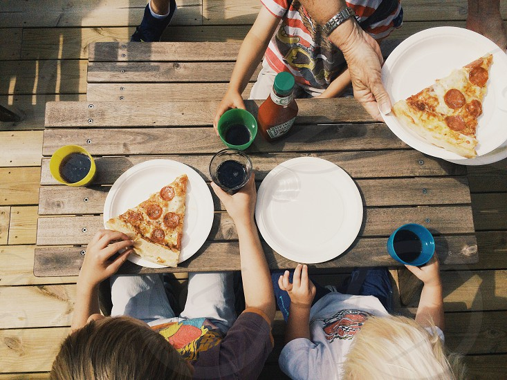 3 children sitting at brown wooden table photo