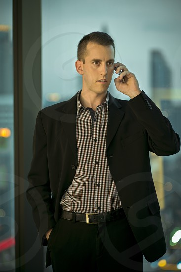 Business  look white Caucasian male wearing suite talking on the phone city building background photo