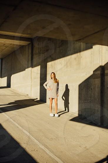 woman in beige dress standing under the concrete bridge photo