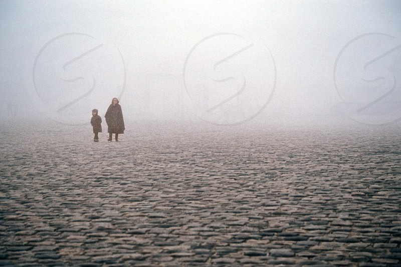 A foggy morning with a mother and child outside the Palace of Versailles in France. Notice the vague outline of the palace gates in the background.  photo