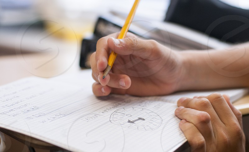 person writing on notebook using yellow pencil photo