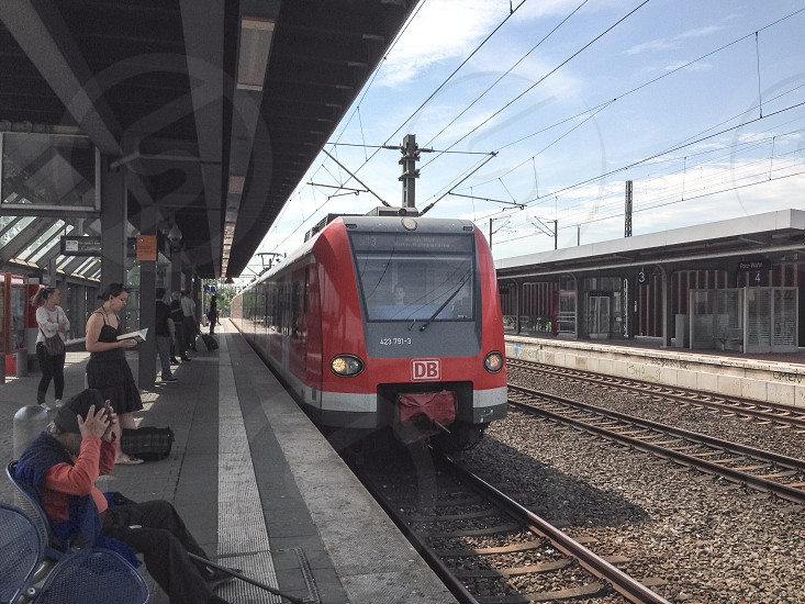 red white and black electric train in station photo