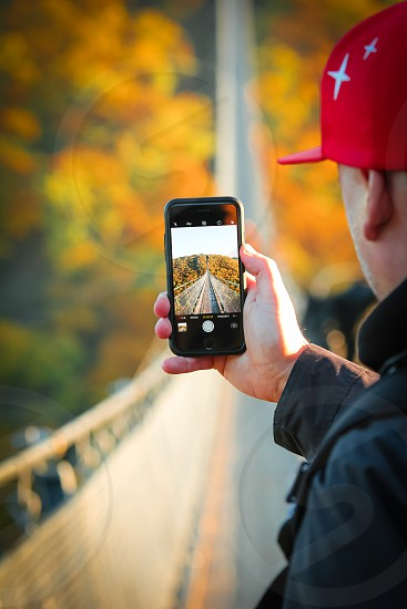 person in black jacket holding space grey iPhone 6 photo