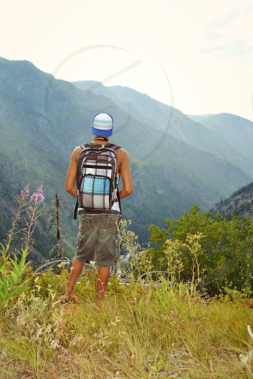 man wearing blue brown and white backpack standing photo