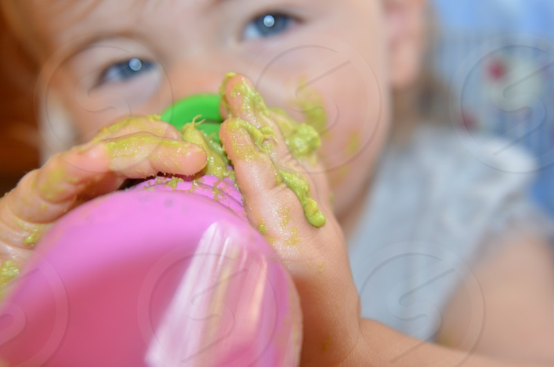 Toddler with avocado on hands drinking from botle photo