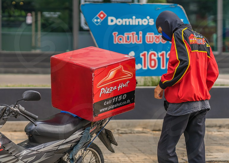 Pizza Hut delivery man in Thailand is parked in front of a Dominio's Pizza sign. photo