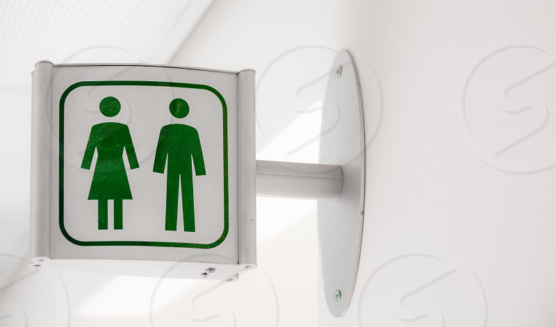Public modern white and green restroom sign on white wallPublic modern white and green restroom sign on white wall. photo