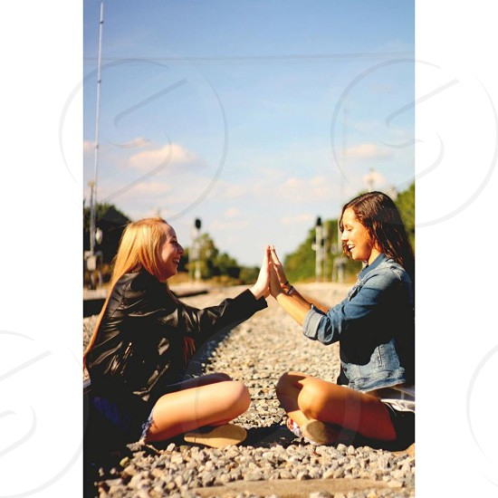 2 woman sitting on the stone and smiling photo