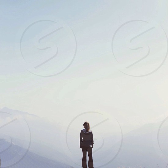 person standing facing the mountains photo