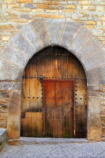 Romanesque arch door wooden medieval village of Ainsa in Spain photo