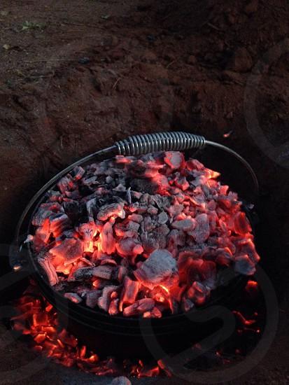 ember charcoal on black metal bucket photo