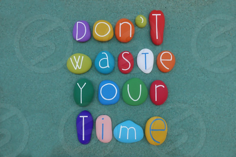 Don't waste your time motivational words composed with colored stones over green sand                                photo