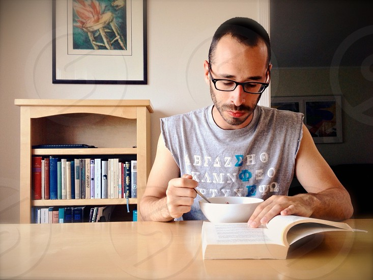 Man sitting at kitchen table eating and reading.  photo