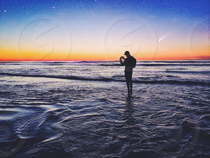 sunset stars man silhouette standing in ocean photo
