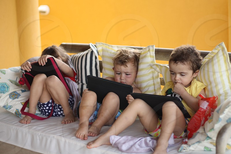 3 boy;s sitting on couch playing tablet games photo
