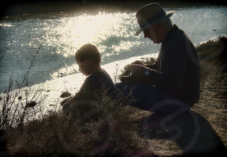Back lit image of a Grandfather and grandson sitting at the edge of a stream having a talk  photo