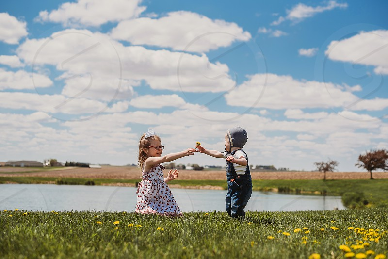 Sisters sharing dandelions while playing in the sunshine. photo