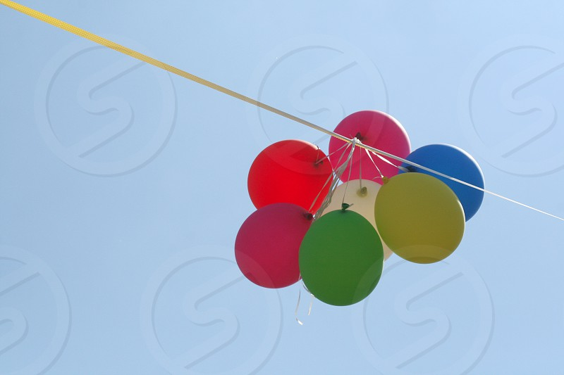 7 balloons tied on string above photo