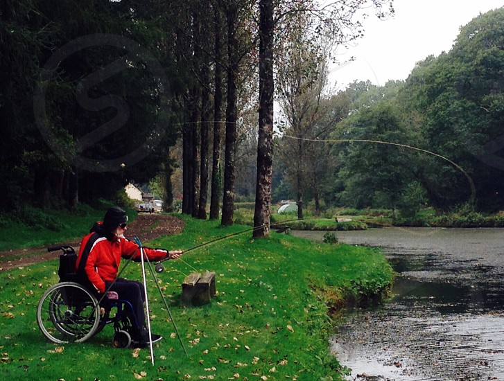 Disabled man fly fishing from wheelchair  photo