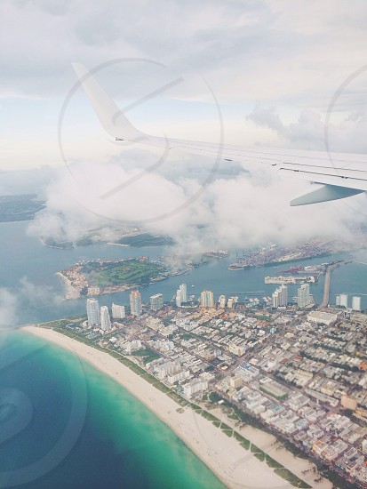 Plane flying over Miami Beach Florida. Looking out of the window down on the city and beach and ocean below.  photo