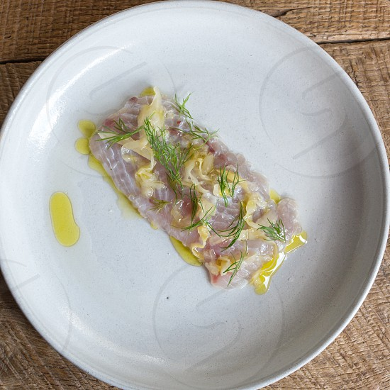 tuna with olive oil on plate at top of table photo