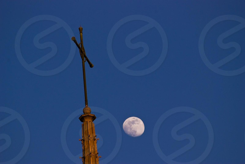church steeple with a cross and the moon in the background photo