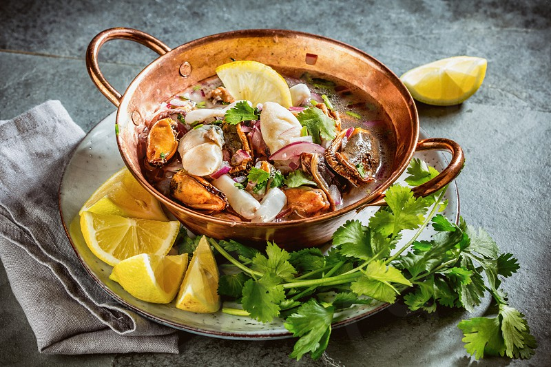 Peruvian Latin American seafood shellfish ceviche cebiche. Raw seafoods - mussels shrimps clams squides marinated in lemon juice with red onion and coriander in cooper bowl gray slate background. photo