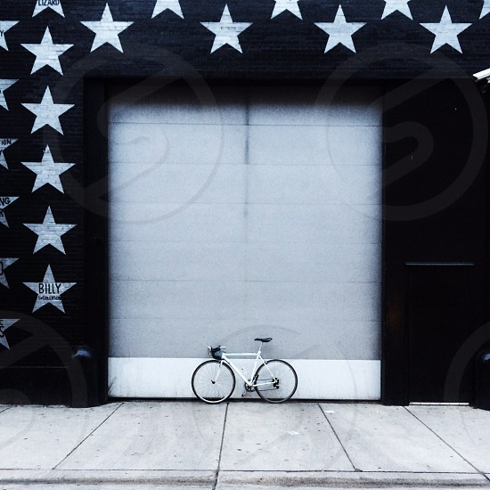 white bicycle in front of a garage photo