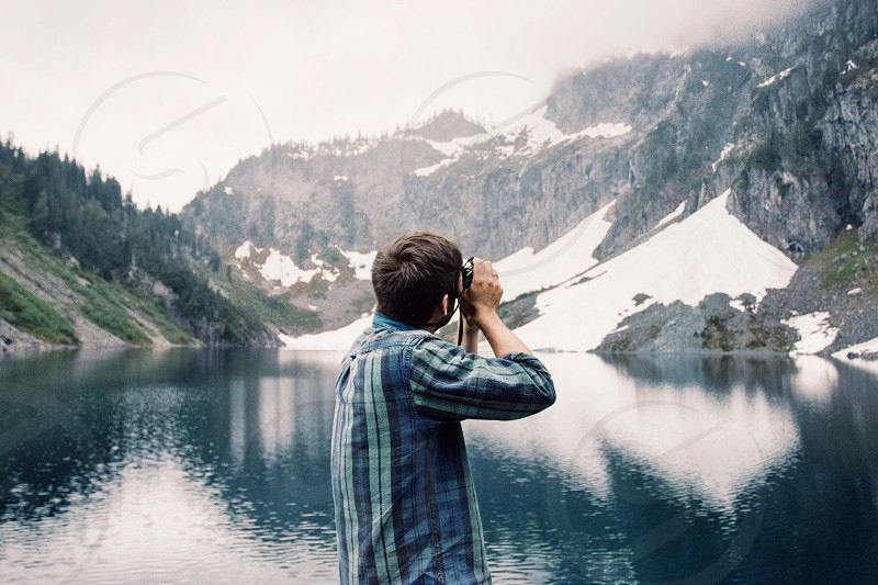 man in blue and green plaid button down shirt photographing a snowy lake photo