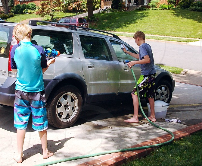Brothers washing the car and shooting water at each other photo