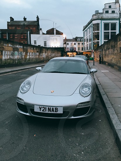 silver porsche 911 parked near concrete wall during daytime photo